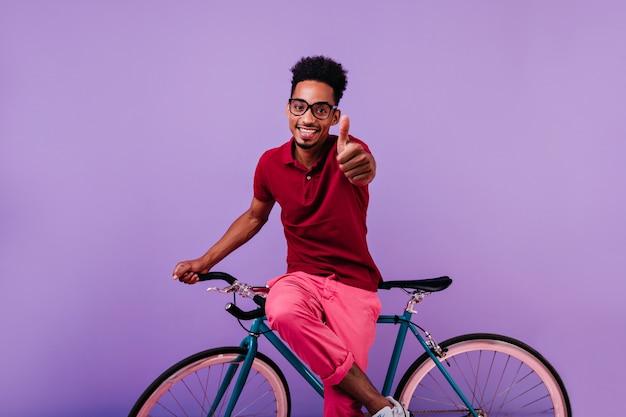 親指を上に向けてポーズをとる眼鏡をかけたインスピレーションを得たアフリカ人。自転車に座って笑っている自信を持って黒人の男。