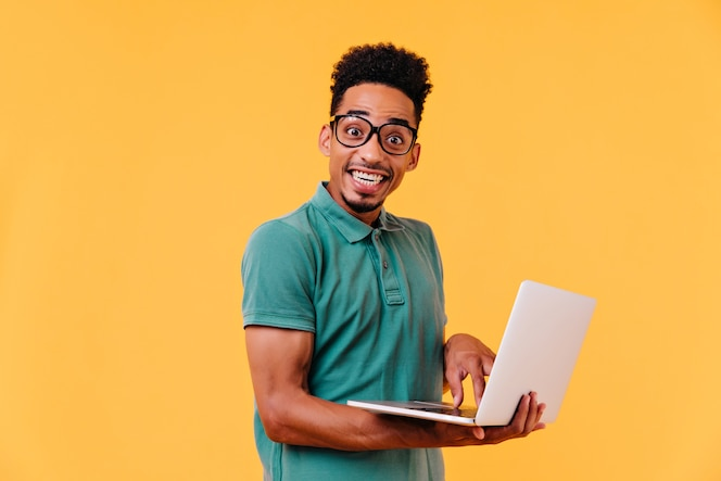 白いラップトップを保持している眼鏡でインスピレーションを得たアフリカの学生。のんきな黒人男性フリーランサーの笑顔。