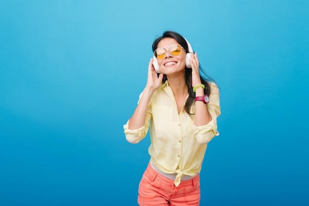 ピンクの腕時計と緑のブレスレットの音楽を聴くことでインスピレーションを得たアジアの女性モデル。オレンジ色のサングラスをかけた恍惚としたラテン系の女の子がヘッドフォンに触れて笑っている室内写真。