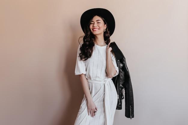 革のジャケットを保持しているインスピレーションを得たアジアの女性。ドレスと帽子のかわいい中国人女性のスタジオショット。