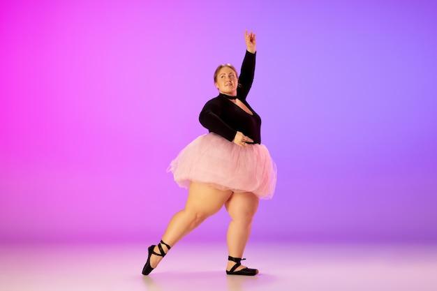 탁월한. 아름다운 백인 플러스 사이즈 모델은 네온 불빛 아래 그라데이션 보라색-분홍색 스튜디오 배경에서 발레 댄스를 연습합니다. 동기 부여, 포함, 꿈 및 성취의 개념.