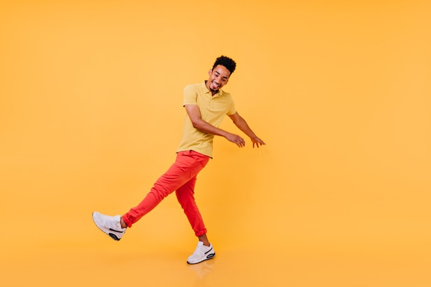 Вдохновленный темнокожий парень в яркой повседневной одежде веселых танцев. смеющийся африканский мужчина-модель в желтой футболке и красных штанах дурачится.