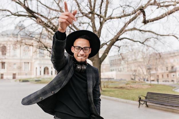 公園で手を振っている灰色のジャケットのインスピレーションを得た黒人の男。街の広場で休んでいる帽子と眼鏡の嬉しいアフリカの男性モデルの屋外の肖像画。