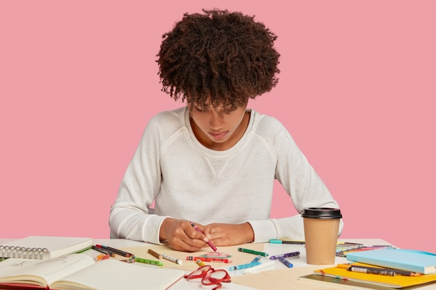 Inspired black young woman enjoys drawing with crayons on blank sheet of paper, focused down, has mood for creativity, creats something original, sits at workplace alone against pink wall