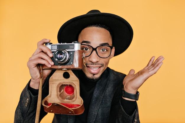Ispirato uomo mulatto dagli occhi marroni tenendo la fotocamera sulla parete gialla. foto dell'interno del primo piano del fotografo maschio africano che gode del lavoro.