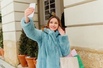 Inspired brown-haired girl making selfie after shopping and laughing.
