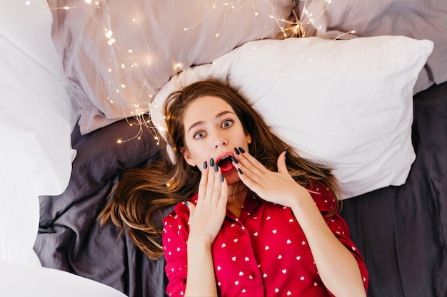 朝のベッドで身も凍るようなインスピレーションを得たブルネットの女の子。かわいいパジャマ姿の夢のような白人女性の頭上の屋内肖像画。