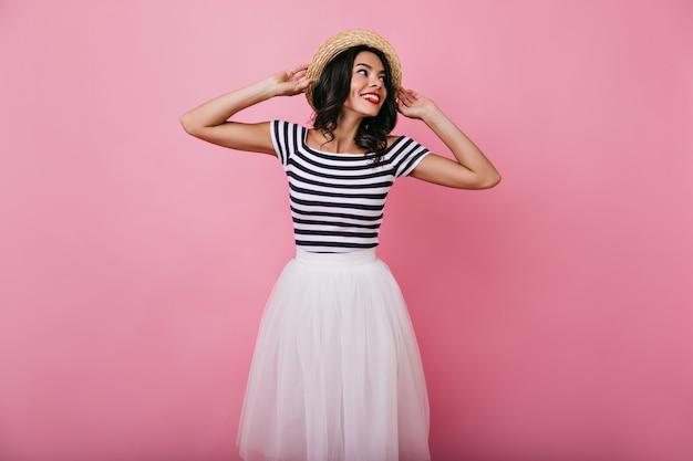 Вдохновленная брюнетка в летней шляпе пугает. загорелая привлекательная женщина в белой юбке с удовольствием.