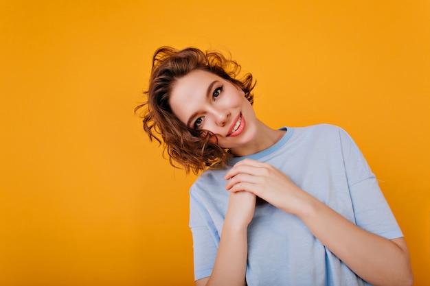 노란색 벽에 기쁨과 함께 포즈 핑크 입술으로 갈색 머리 소녀 영감. 파란색 복장에 사랑스러운 백인 여자의 스튜디오 샷.