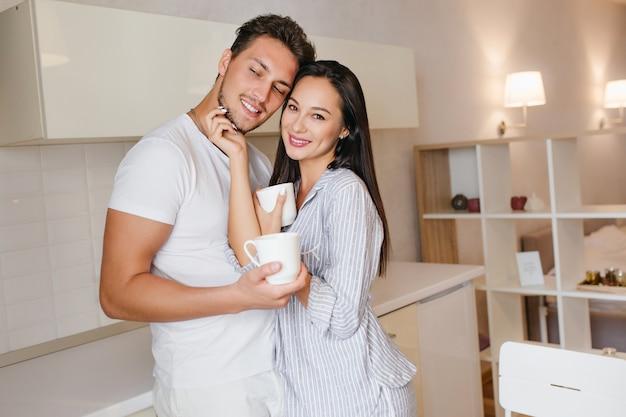 Ispirata donna bruna che accarezza il viso del marito mentre beve caffè