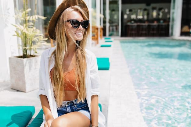 水の近くで休んでいる流行の黒い眼鏡のインスピレーションを得た白人女性。
