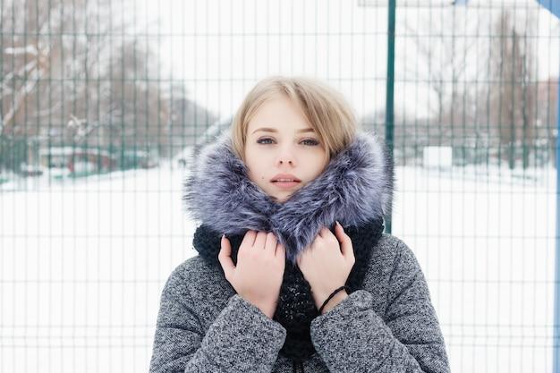 겨울 아침에 포즈를 취하는 동안 모직 스카프를 입은 백인 여성이 미소를 지으며 멀리 바라보고 있습니다. 눈 덮인 마당에 서 있는 매력적인 여성의 클로즈업 초상화. 추운 화창한 날씨입니다. 여자 겨울 개념입니다.