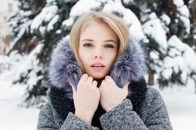 Inspired caucasian woman in woolen scarf looking away with smile while posing in winter morning. close-up portrait fascinating female standing in snowy yard. cold sunny weather. woman winter concept.