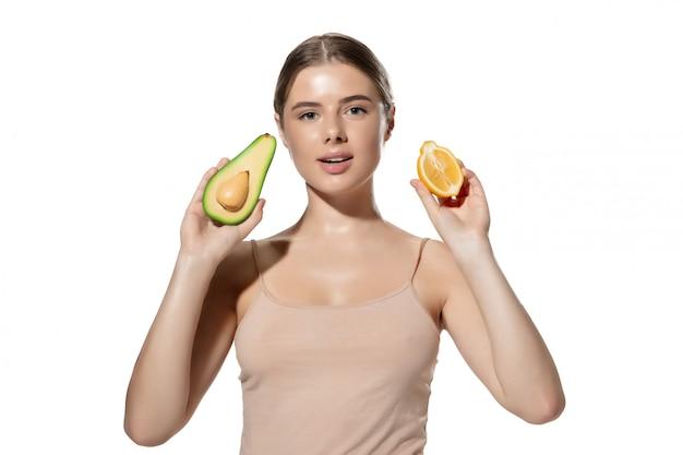 Вдохновленный. закройте вверх красивой молодой женщины с зелеными листьями на ее стороне над белизной. косметика и макияж, натуральные и эко-процедуры, уход за кожей