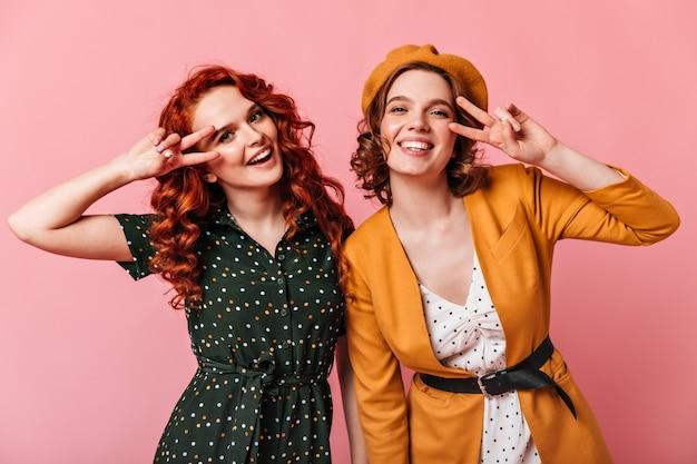 Ragazze ricci ispirate che mostrano il segno di pace. studio shot di splendide donne caucasiche gesticolando su sfondo rosa.