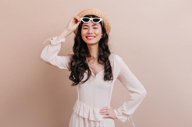カメラに微笑んでインスピレーションを得た巻き毛の韓国人女性。ベージュの背景に分離されたサングラスでロマンチックなアジアの若い女性の正面図。