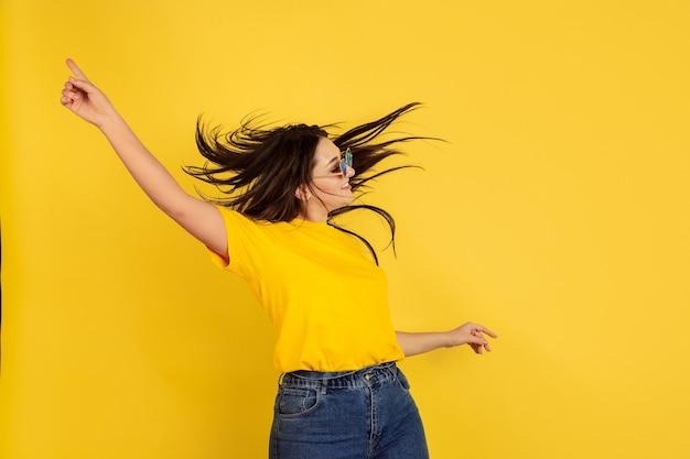 선글라스에서 영감을 얻은 춤. 노란색 벽에 백인 여자입니다. 캐주얼 스타일에 아름 다운 여성 갈색 머리 모델입니다. 인간의 감정, 표정, 판매, 광고, copyspace의 개념.