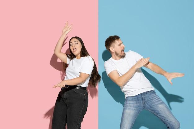 Вдохновленный. танцы, движения, веселье. молодой и счастливый мужчина и женщина в повседневной одежде на розовой, синей двухцветной стене. понятие человеческих эмоций, выражения лица, отношений, рекламы. прекрасная пара.