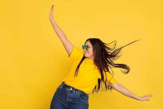 Inspired dancing in sunglasses. caucasian woman on yellow  wall. beautiful female brunette model in casual style. concept of human emotions, facial expression, sales, ad, copyspace.