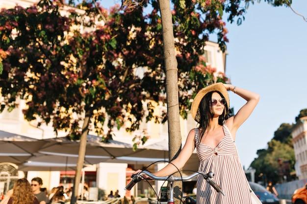 Вдохновленная темноволосая девушка в модной шляпе смотрит в сторону, стоя с велосипедом в летнем кафе в европейском городе