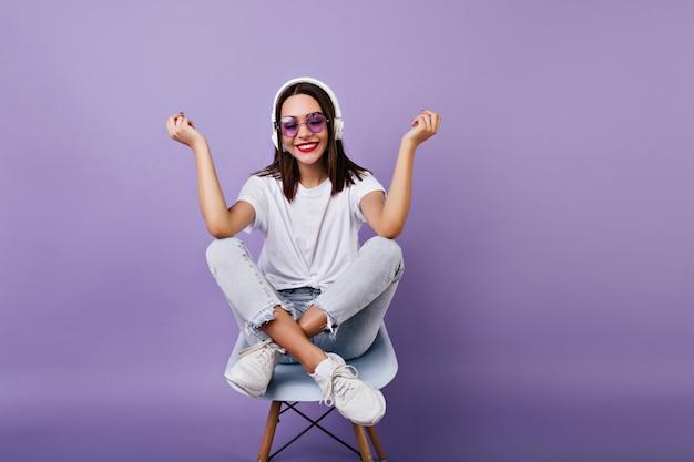 椅子に座って笑っているインスピレーションを得た黒髪の少女。白い服とヘッドフォンで笑顔の素晴らしい女性モデルの屋内写真。