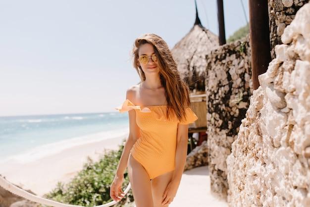 エキゾチックなリゾートで自然の景色を楽しむインスピレーションを得た黒髪の白人の女の子。オレンジ色の水着ポーズで壮大な日焼けした女性の屋外の肖像画