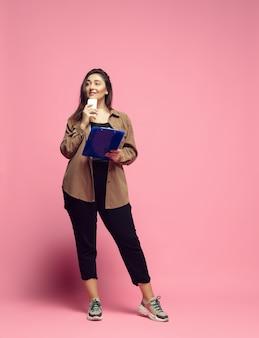 Вдохновленный, мечтательный. молодая женщина в повседневной одежде на розовом фоне. бодипозитивный персонаж, феминизм, любящая себя, концепция красоты. деловая женщина больших размеров, красивая девушка. включение, разнообразие.