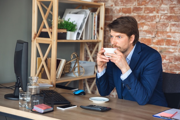 Inspired drinking coffee, dreamful. young man, manager return to work in his office after quarantine, feels happy and inspired. coming back to normal life. business, finance, emotions concept.