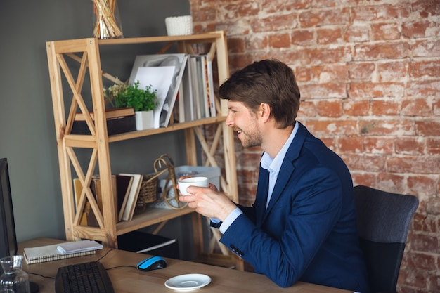Inspired drinking coffee reading tasks young man manager return to work in his office