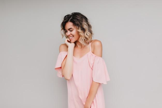 Вдохновленная европейская девушка в стильной одежде позирует с застенчивой улыбкой. портрет очаровательной белой дамы в розовом платье.