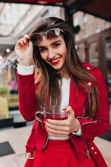 都市空間で笑っている明るい化粧のインスピレーションを得たヨーロッパの女の子