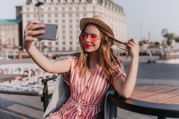 麦わら帽子をかぶったヨーロッパの女性にインスピレーションを得て、髪の毛で遊んだり、自分撮りをしたりしています。街で自分の写真を撮るストライプのドレスを着た愛らしい白人の女の子の屋外写真。