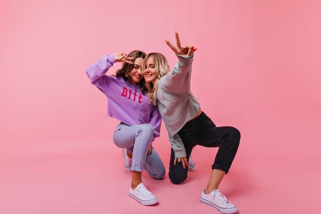 ピースサインでポーズをとる黒いズボンのインスピレーションを得た金髪の女性。彼女の妹と一緒に時間を過ごすジョクンドブルネットの女の子。 無料写真