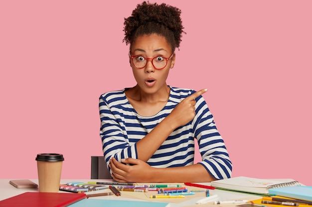영감을받은 여성 아티스트가 스케치를 그리고 스케치북을 사용하며 직장에서 포즈를 취하고 분홍색 벽에 빈 공간을 검지 손가락으로 가리 킵니다. 충격을받은 화가는 커피를 마시고 크레용으로 물감을 칠해