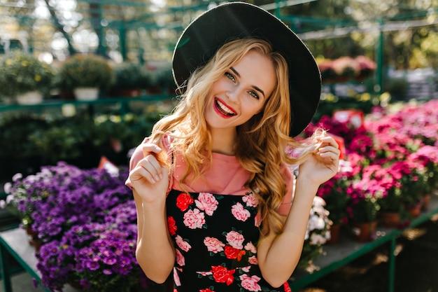 カラフルな花のフリントに立っている帽子のインスピレーションを得た女性モデル。オレンジリーでリラックスした魅力的な盲目の女性の肖像画。