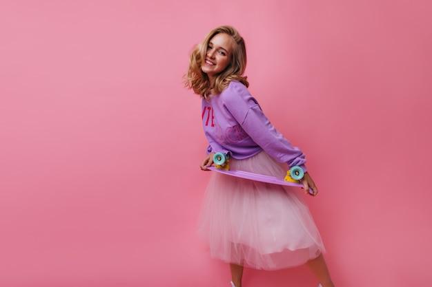 Вдохновленная женская модель смеется, позируя с милым скейтбордом. очаровательная юная леди с блестящими волосами, держащая longboard.