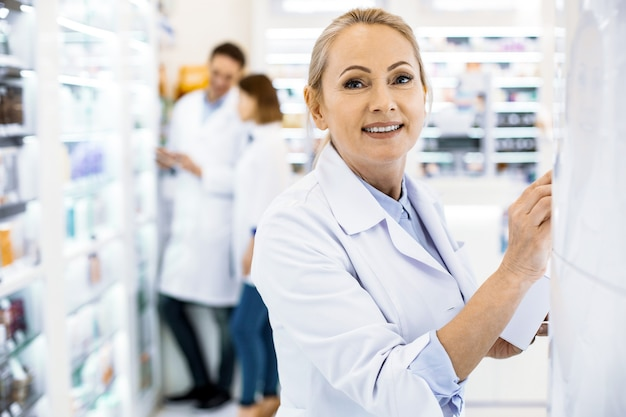 Inspired female pharmacist posing on blurred background and looking at camera