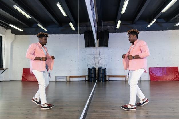全身鏡の前に立ってダンススキルを検査するピンクのシャツを着たインスピレーションを得た柔軟な男