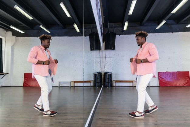 Inspired flexible man in pink shirt standing in front of full length mirror and inspecting dancing skills