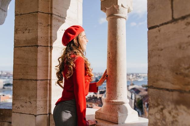 Ragazza francese ispirata con l'acconciatura riccia in piedi vicino a colonne di pietra e godendo di viste sulla città