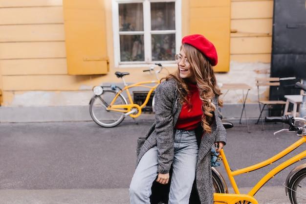 Ragazza ispirata in blue jeans in posa per strada e guardandosi intorno con una risata sincera