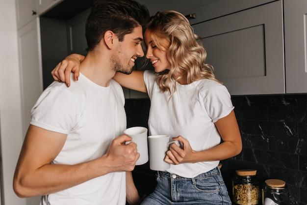 夫と一緒に朝を楽しんでいるインスピレーションを得た女の子。コーヒーを飲む冷たいカップルの屋内の肖像画。