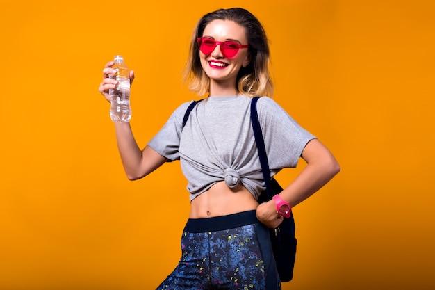水のボトルを押しながら笑みを浮かべて短い髪型と赤いサングラスで触発された女の子。黄色の背景に分離されたヨーロッパの女性モデルを笑いの屋内ポートレート。