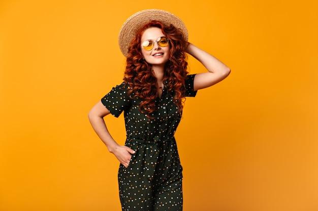 Вдохновленная девушка в соломенной шляпе позирует с рукой в кармане. студия сняла блаженную улыбающуюся рыжую женщину в солнечных очках, стоя на желтом фоне.