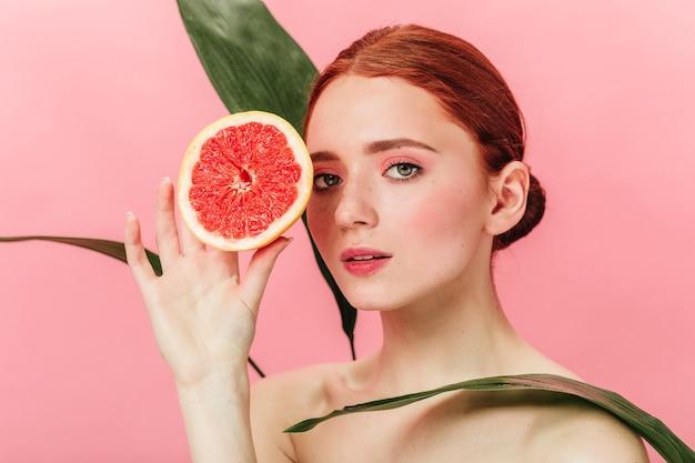 緑の葉と柑橘類でポーズをとるインスピレーションを得た女の子。ピンクの背景にグレープフルーツが立っている生姜の女性のスタジオショット。