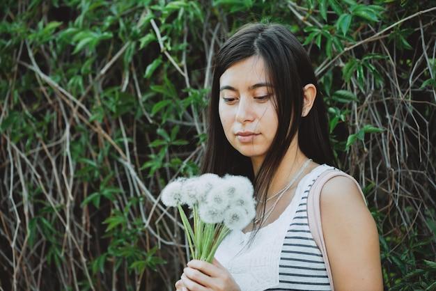 여름 녹지 가운데 정원에서 무성 한 민들레 부케와 영감을 된 소녀. 봄 시간에 녹색 헤 지 근처 blowball 꽃과 국가 소녀. 아름 다운 여성의 초상화입니다. 메이크업이없는 자연스러운 아름다움.