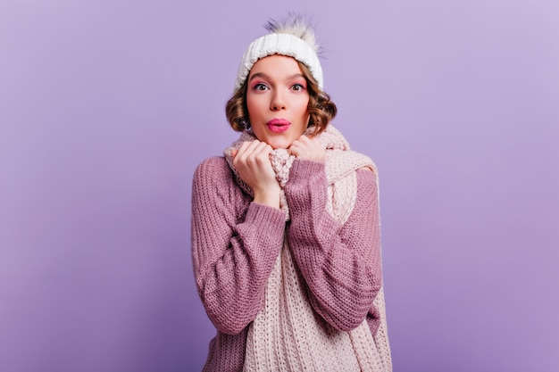 Inspired girl with pink makeup and surprised smile posing on purple wall.  cute young woman in hat and scarf expressing happiness.