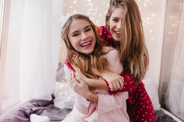 아침에 친구를 포용하는 진지한 미소로 영감을 얻은 소녀. 긴 머리를 가진 긍정적 인 자매는 침실에서 포옹합니다.