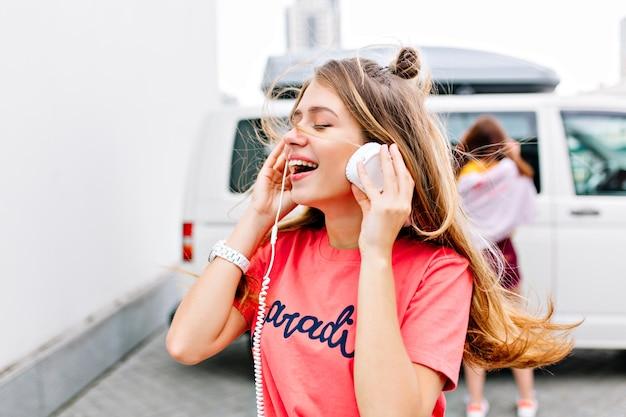 Ragazza ispirata con l'acconciatura alla moda in camicia rosa alla moda che gode della buona canzone con il sorriso e gli occhi chiusi