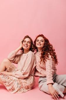 진지한 미소로 바닥에 포즈를 취하는 영감을받은 소녀. 분홍색 배경에 행복 친구의 스튜디오 샷입니다.
